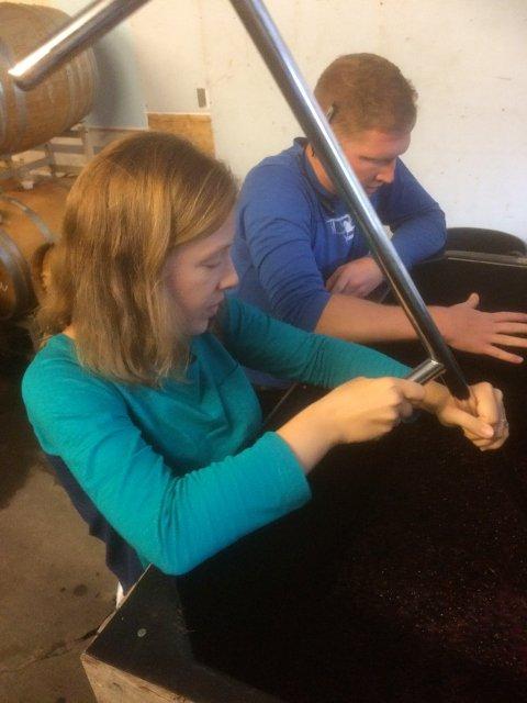 Abby y Scott removiendo el vino en Barnstormer Winery